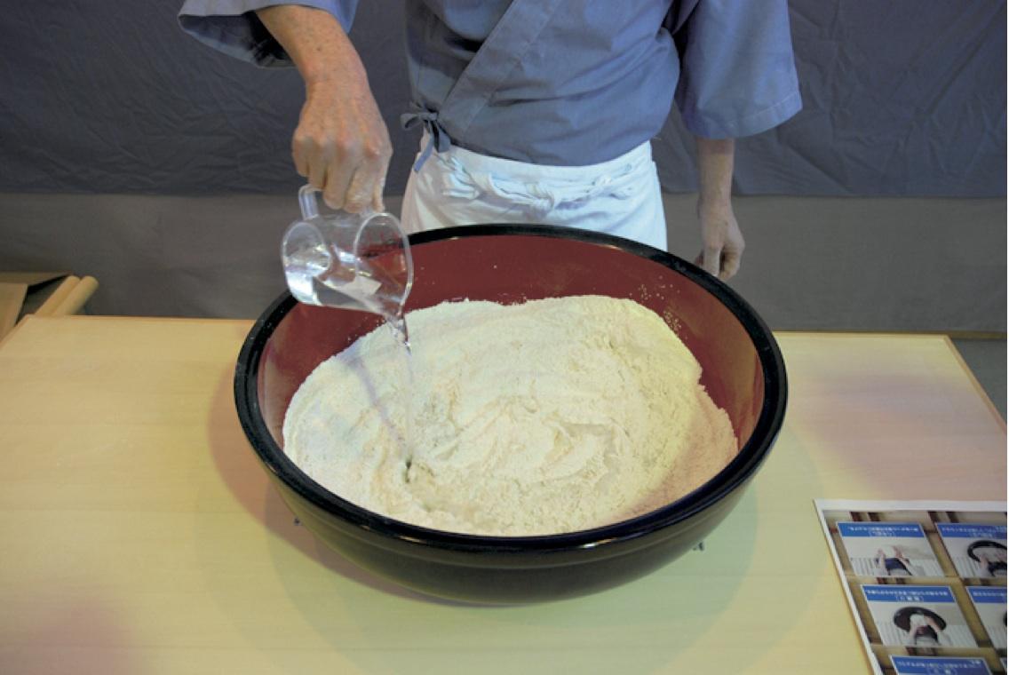 (1)みずまわし -ふるいを使ってそば粉半量、小麦粉、そば粉半量の順にそば鉢に入れて混ぜ、用意した水の約半量を入れてよく混ぜる。