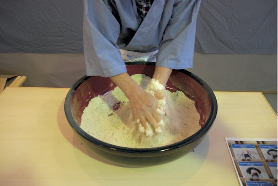 (2)水まわし -粉がパン粉状になったら残りの半分の量の水を加えさらに混ぜる。
