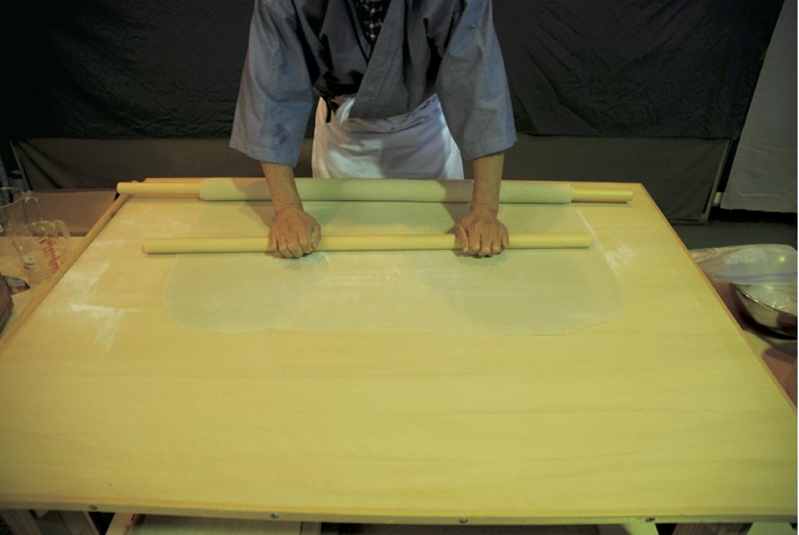 (11)本延し -四角くなった麺帯を凸凹がなくなり厚さ1.5mm程度になるまで麺棒で平に延す。