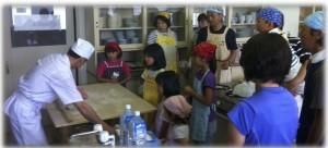 お手本を見せる一人さんの作業をくいいるように見つめる参加者たち(2011年8月6日)